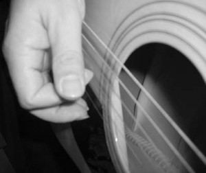 Holding your plectrum, plucking the string.