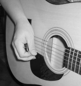Holding plectrum, striking the string.